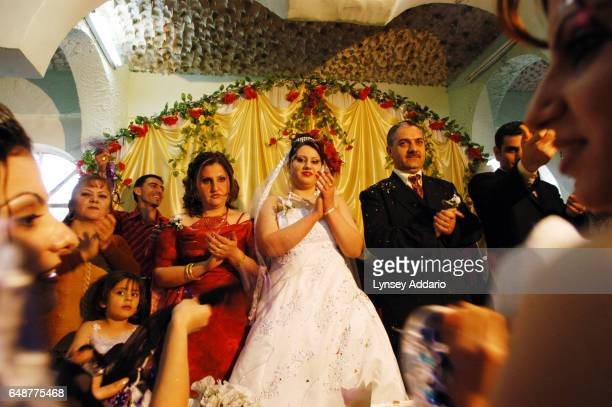 An Iraqi bride and groom are greeted and celebrated by guests during their wedding ceremony at a wedding hall in Baghdad Iraq February 18 2004 Sohar...