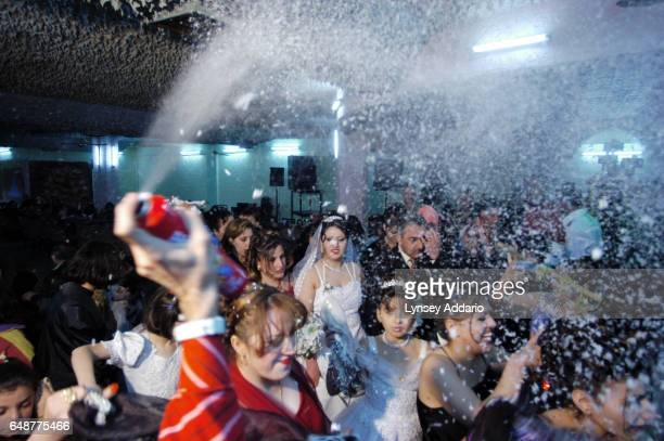 An Iraqi bride and groom walk under foam during their wedding ceremony at a wedding hall in Baghdad Iraq February 18 2004 Sohar a member of Iraq'a...