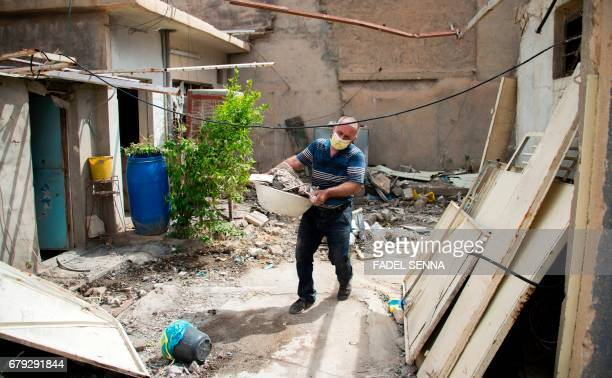An Iraqi carries away garbage from his house after his return to his hometown in the predominantly Christian Iraqi town of Qaraqosh which lies some...