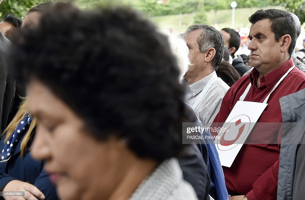 An Iraqi catholic pilgrim with a sign attached around his neck showing the 'Nazarene' (a symbol painted on Christian's houses in Iraq to locate them) prays with others during the feast of the Assumption on August 15, 2014 in the sanctuary of Our Lady in the French Southwestern pilgrimage city of Lourdes.