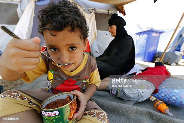 An Iraqi child eats canned food at a temporary camp set up to house civilians fleeing violence in Iraq's northern Nineveh province in Aski kalak 40...