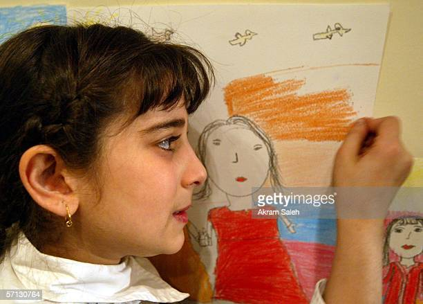 An Iraqi child paints and draws on March 19 2006 in Baghdad Iraq The Iraqi Ministry of Culture organized the exhibition for the paintings of children...