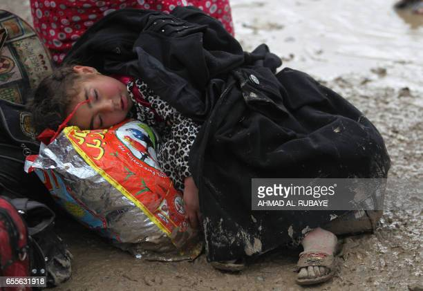 TOPSHOT An Iraqi child rests as residents from Mosul arrive at the Hamam alAlil camp for displaced people on March 20 during the government forces...