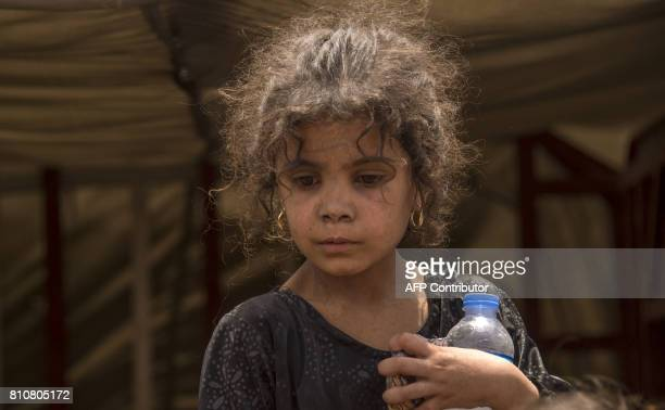 An Iraqi child who fled the fighting between government forces and Islamic State group jihadists in the Old City of Mosul holds a water bottle as she...