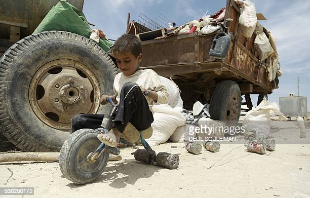 TOPSHOT An Iraqi child who fled with his family the northern province of Nineveh following the advance of jihadists of the Islamic State group plays...