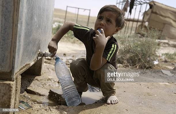 An Iraqi child who fled with his family the northern province of Nineveh following the advance of jihadists of the Islamic State group fills a bottle...