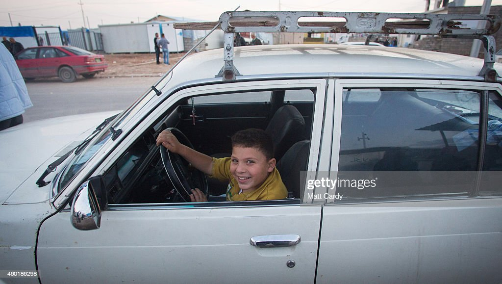 An Iraqi Christian boy, who fled from his home because of Islamic State's advance earlier this year, sits at the wheel of a car at the entrance to a camp near Umm al-Nour Church, which is now home to hundreds of displaced Iraqi Christians on December 8, 2014 in Erbil, Iraq. Although the autonomous Kurdistan region in northern Iraq was already a refuge for an estimated 250,000 Syrian refugees, since the Islamic State began its onslaught on Iraq in June, Kurdistan has also taken in a more than one and a half million displaced people. Many have been placed in purpose-built refugee camps but the huge numbers mean thousands of others are forced to live in un-finished buildings or inadequate, makeshift shelters and as winter in the region closes in, there are growing concerns for the welfare of the refugees who, while their homes are still in ISIL controlled territory, have no realistic prospect of returning to them.
