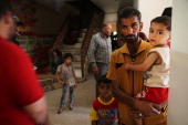 An Iraqi Christian family walk through Saint Joseph's church where they are living with hundreds of other Christians after having to flee their...