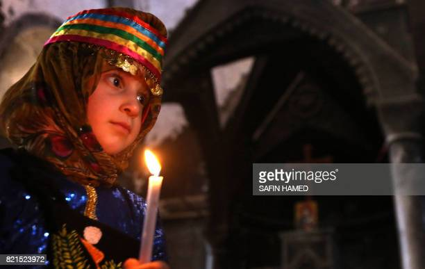 An Iraqi Christian girl holds a candle as she attends a mass at the Church of the Immaculate Conception on July 24 2017 in the predominantly...