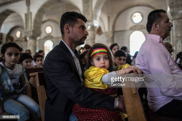 An Iraqi Christian girl sits with her father during an easter ceremony at Saint John's Church in the nearly deserted predominantly Christian Iraqi...