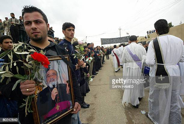 An Iraqi Christian man holds a framed picture of Archbishop Paulos Faraj Rahho as he stands amid mourners during his funeral in the northern Iraqi...