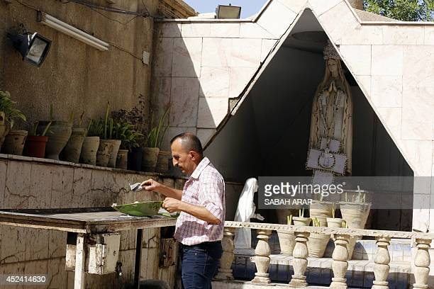 An Iraqi Christian man lights a candle outside the Virgin Mary Chaldean church in the Karrada neighborhood of the capital Baghdad on July 20 2014...