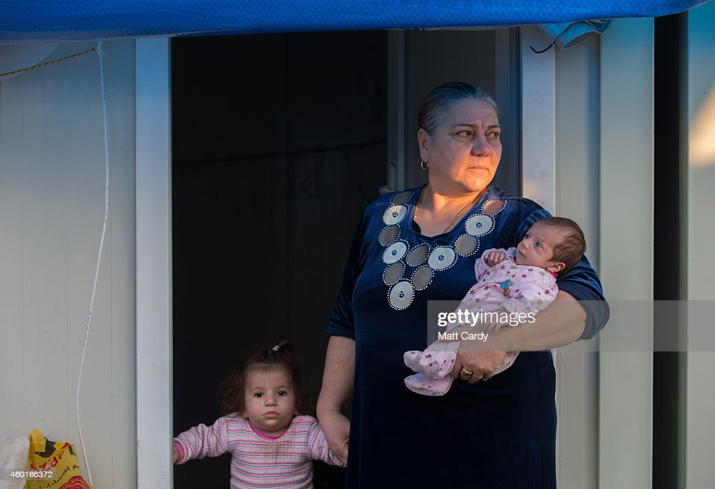 An Iraqi Christian, who fled from her home because of Islamic State's advance earlier this year, stands in the doorway of her temporary home at a camp near Umm al-Nour church which is now home to hundreds of displaced Iraqi Christians on December 8, 2014 in Erbil, Iraq. Although the autonomous Kurdistan region in northern Iraq was already a refuge for an estimated 250,000 Syrian refugees, since the Islamic State began its onslaught on Iraq in June, Kurdistan has also taken in a more than one and a half million displaced people. Many have been placed in purpose-built refugee camps but the huge numbers mean thousands of others are forced to live in un-finished buildings or inadequate, makeshift shelters and as winter in the region closes in, there are growing concerns for the welfare of the refugees who, while their homes are still in ISIL controlled territory, have no realistic prospect of returning to them.