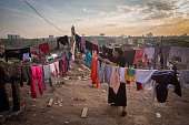 An Iraqi Christian who fled from her home because of Islamic State's advance earlier this year hangs up washed clothes to dry besides a displaced...