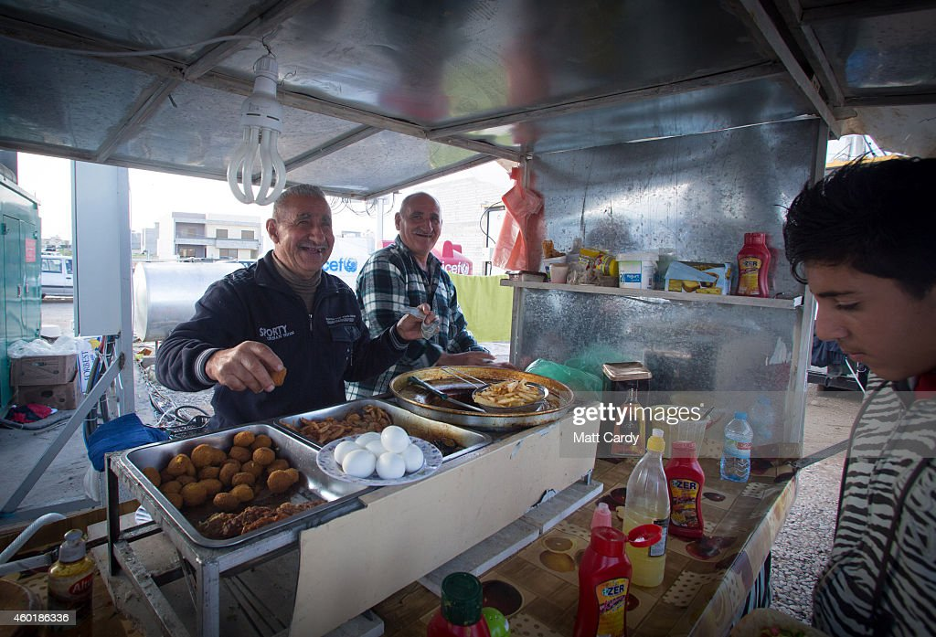 An Iraqi Christian, who fled from his home because of Islamic State's advance earlier this year, sells hot food at the entrance to a camp near Umm al-Nour Church, which is now home to hundreds of displaced Iraqi Christians on December 8, 2014 in Erbil, Iraq. Although the autonomous Kurdistan region in northern Iraq was already a refuge for an estimated 250,000 Syrian refugees, since the Islamic State began its onslaught on Iraq in June, Kurdistan has also taken in a more than one and a half million displaced people. Many have been placed in purpose-built refugee camps but the huge numbers mean thousands of others are forced to live in un-finished buildings or inadequate, makeshift shelters and as winter in the region closes in, there are growing concerns for the welfare of the refugees who, while their homes are still in ISIL controlled territory, have no realistic prospect of returning to them.