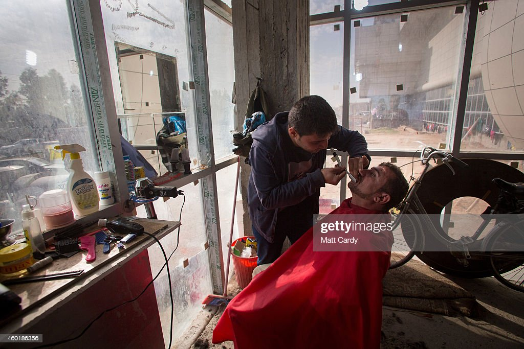 An Iraqi Christian, who fled from his home because of Islamic State's advance earlier this year, operates a barber shop inside the entrance hall of the unfinished Ankawa Shopping Mall which is now home to hundreds of displaced people on December 8, 2014 in Erbil, Iraq. Although the autonomous Kurdistan region in northern Iraq was already a refuge for an estimated 250,000 Syrian refugees, since the Islamic State began its onslaught on Iraq in June, Kurdistan has also taken in a more than one and a half million displaced people. Many have been placed in purpose-built refugee camps but the huge numbers mean thousands of others are forced to live in un-finished buildings or inadequate, makeshift shelters and as winter in the region closes in, there are growing concerns for the welfare of the refugees who, while their homes are still in ISIL controlled territory, have no realistic prospect of returning to them.