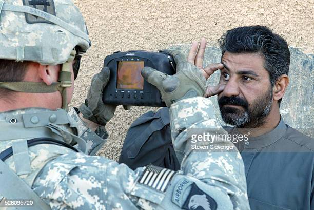 An iraqi citizen has his eye scanned by a US soldier with the 1st Squadron 33rd Cavalry Regiment in Hoy Al Askariah a small town south of Baghdad The...