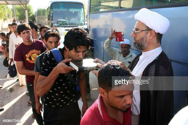 An Iraqi civilian volunteering to fight a militant offensive kisses a Koran book as he queues with comrades before boarding buses to reach Mosul on...