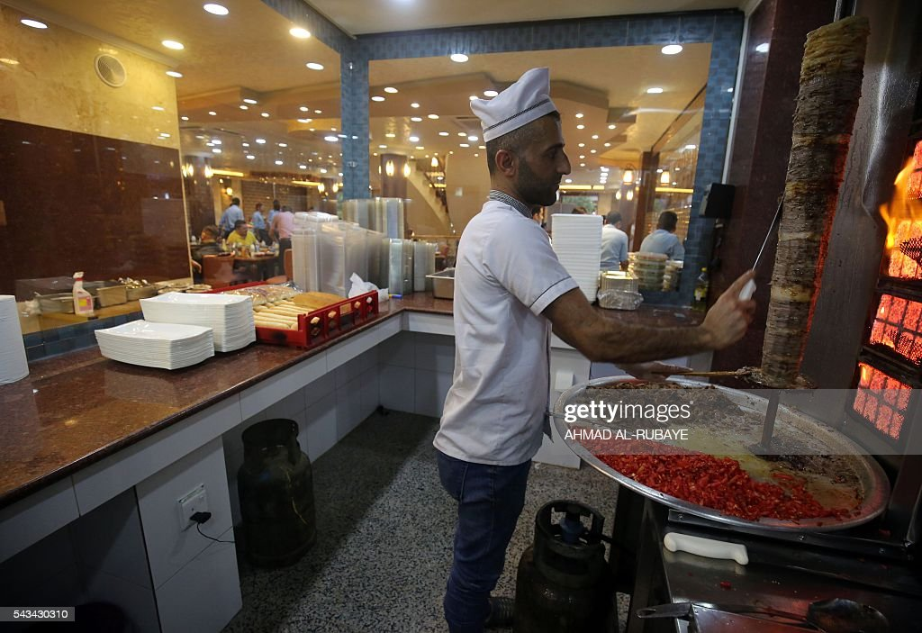 Iraqi workers prepare food in the kitchen at a restaurant where customers come to break the fast with an Iftar diner during the Muslim feating month of ramadan on June 28, 2016 in the capital Baghdad. / AFP / AHMAD