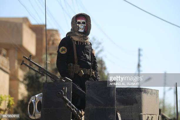 TOPSHOT An Iraqi counter terrorism forces member stands guard in the Mosul alJadida area on March 26 following air strikes in which civilians have...