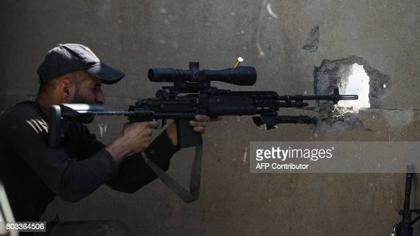 An Iraqi CounterTerrorism Service sniper takes a shot during the advance towards the Grand Mosque of Nuri in the Old City of Mosul on June 29 as the...