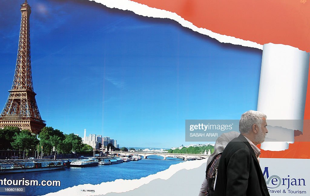 An Iraqi couple walks past a giant advert making the promotion of a travel agency organizing trips to Paris, a new destination for the country, on February 6, 2013 in the Iraqi capital, Baghdad. Iraqis are now allowed to ask for European visas. AFP PHOTO SABAH ARAR