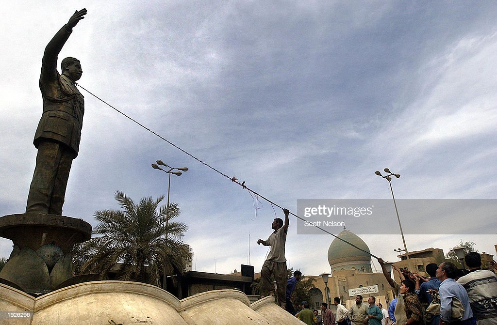 An Iraqi crowd tries to pull down a statue of ousted Iraqi President Saddam Hussein during an impromptu celebration on the streets April 12, 2003 in downtown Baghdad, Iraq. The crowd at first tried to topple the large statue but when they could not, it was set on fire instead while chanting anti-Saddam Hussein slogans.