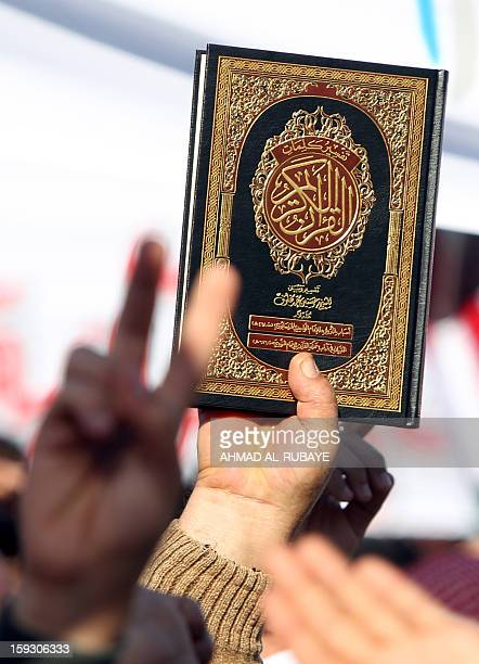 An Iraqi demonstrator holds a copy of the Koran Islam's holy book during an antigovernment protest outside the Sunni Umm alQura mosque in Baghdad on...