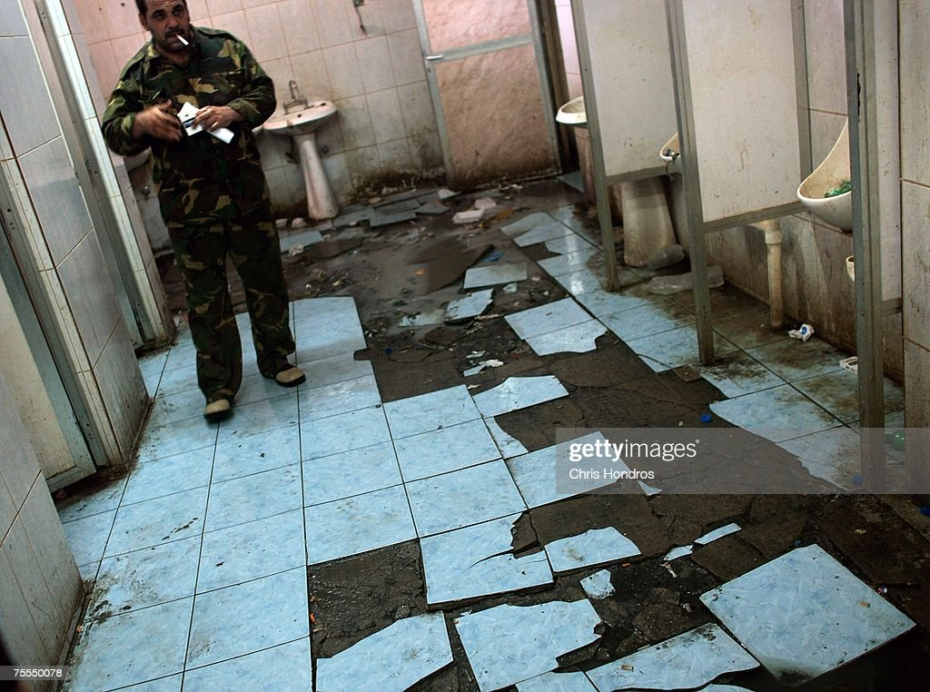 An Iraqi detainee walks in sewage on the floor of a decrepit bathroom at an Iraqi government holding pen July 19, 2007 at Forward Operating Base Justice, a joint US-Iraqi base in Baghdad, Iraq. Nearly a thousand 'detainees' are held in a series of rooms at the detention center, in an area intended to temporarily hold 300. Many have been held for months without trials or hearings. A human-rights observer employed by the U.S. government has repeatedly complained about the conditions, with problems including overcrowding, intermittent meals, backed up sewage, and long-term detentions in a short-term facility, but conditions have remained the same.
