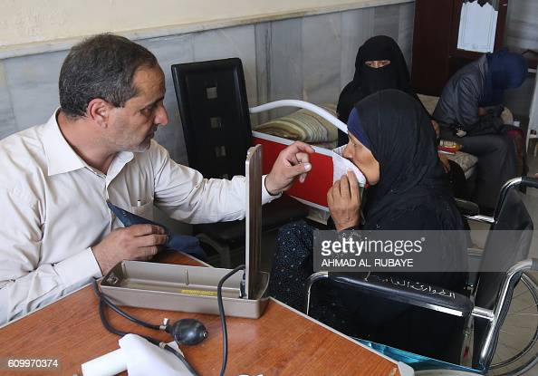 An Iraqi doctor examines a woman in the town of Sharqat around 80 kilometres south of the city of Mosul on September 23 the day after government...
