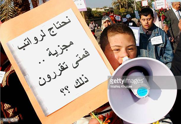 An Iraqi Down syndrome child carries a megaphone and a placard that reads in Arabic 'We need wages when will you take a decision on that' on December...