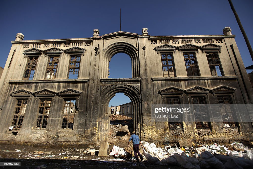 An Iraqi dumps a garbage bag in Baghdad on February 3, 2013, next to the ruins of the Ottoman-era Serail (government building) that was looted and burnt during the US invasion of Baghdad.