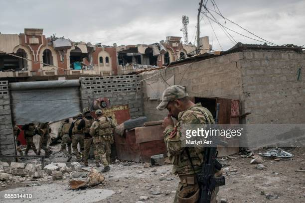 An Iraqi Emergency Response Division soldier lights a cigarette as his unit advances into Bab alTob a neighbourhood in the Old City of west Mosul...