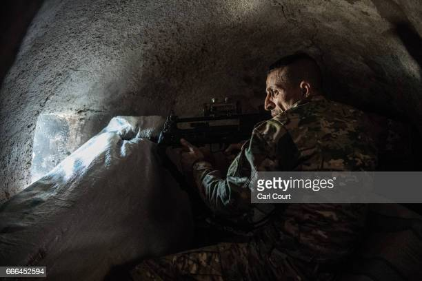 An Iraqi Emergency Response Division soldier looks through a hole in the wall of a house as he watches for Islamic State fighters during fighting in...