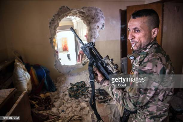 An Iraqi Emergency Response Division soldier prepares to pass through a hole made between buildings during fighting in west Mosul on April 7 2017 in...