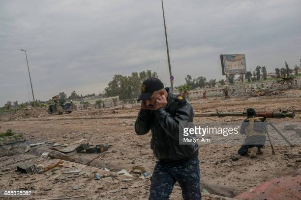 An Iraqi Emergency Response soldier fires an RPG grenade launcher at an Islamic State position during his unit's advance into Bab alTob a...