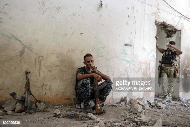An Iraqi Federal Police member smokes as an Iraqi elite Rapid Response Division member wipes his forehead inside a building in Mosul's western...