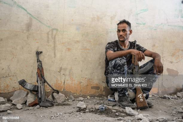 An Iraqi Federal Police member takes a break inside a building in Mosul's western AlShifa district as they battle against Islamic State group...