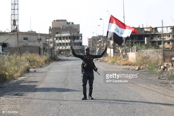 An Iraqi federal police member waves his country's national flag as he celebrates in the Old City of Mosul on July 9 2017 after the government's...