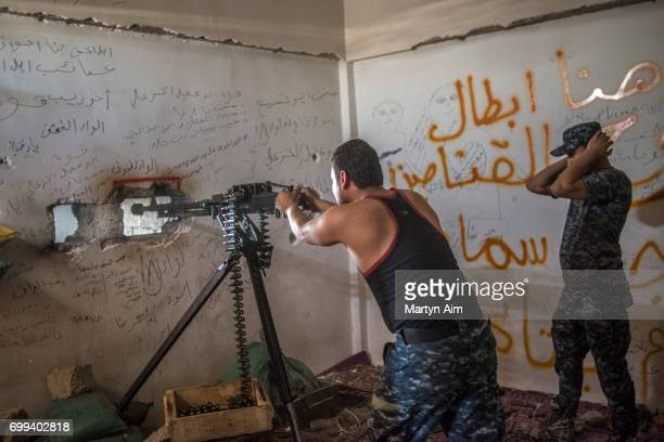 An Iraqi Federal Police soldier fires a 50 calibre machine at Islamic State militants in Bab Jded west Mosul Iraq on June 21 2017 Islamic State...