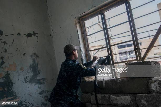 An Iraqi Federal Police soldier fires his machinegun at an Islamic State position from a bulding in Bab alTob a neighbourhood in the Old City of west...
