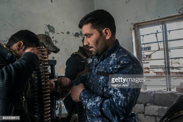 An Iraqi Federal Police soldier loads his machinegun before firing at an Islamic State position from a bulding in Bab alTob a neighbourhood in the...