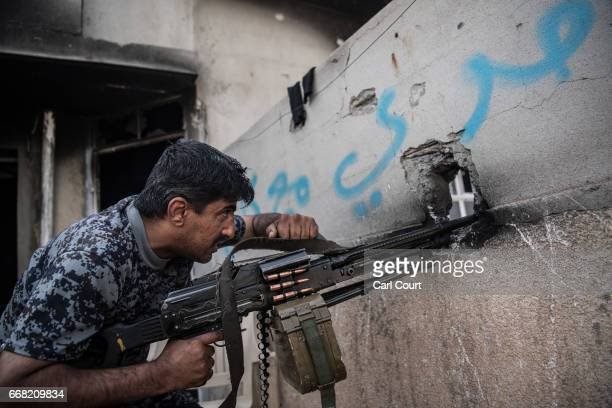 An Iraqi federal policeman fires a machine gun at an Islamic State position on a nearby rooftop during the battle to recapture west Mosul on April 12...