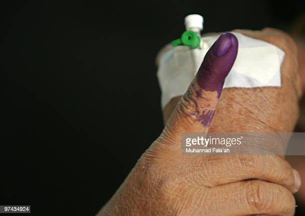 An Iraqi female patient shows her inked finger after voting in the country's parliamentary elections at a special polling station on March 4 2010 in...