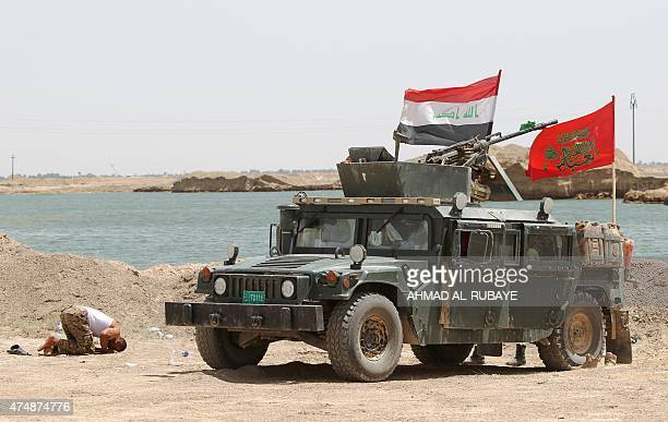 An Iraqi fighter from the popular mobilisation unit prays in alNibaie area northwest of Baghdad on May 27 ahead of an operation aimed at cutting off...