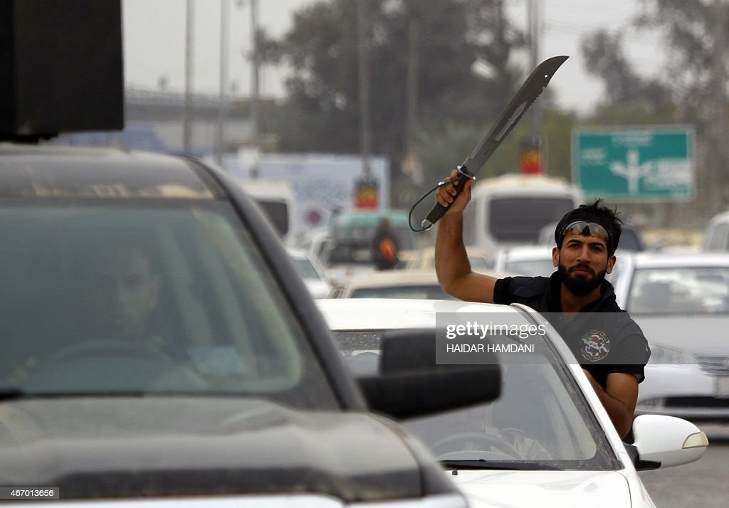An Iraqi fighter from the Saraya alSalam a group formed by Iraqi Shiite Muslim cleric Moqtada alSadr waves a machete as he leaves from the holy city...