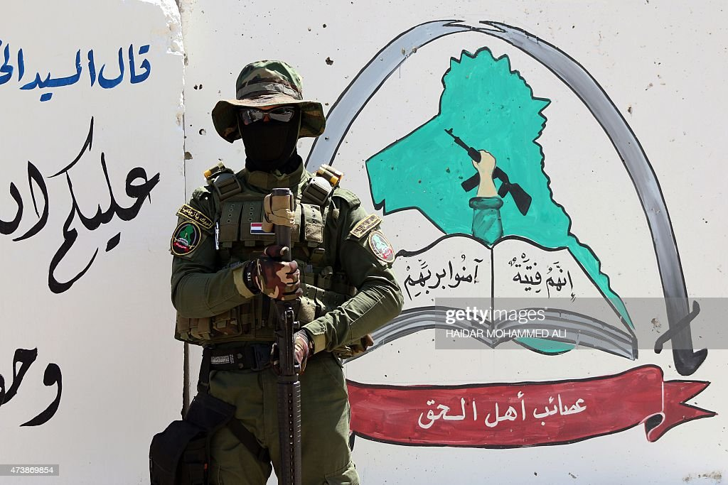 An Iraqi fighter of the Shiite group Asaib Ahl alHaq stands guard outside the militia's headquarters on May 18 2015 in the Iraqi mainly Shiite...