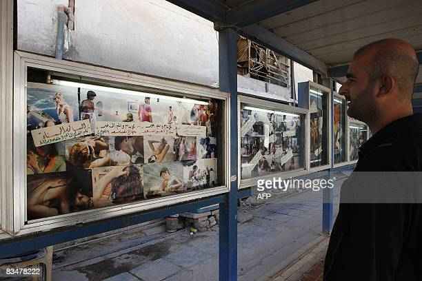 An Iraqi film goer look at the posters of current or upcoming presentations at the entrance of the Atlas cinema one of the most famous movie theatres...