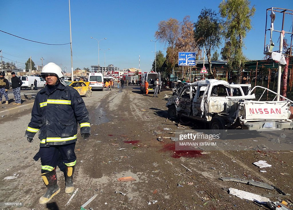 An Iraqi firefighter walks past the scene of a car bombing followed by an assault by grenade-throwing gunmen on a police headquarters in a disputed northern city of Kirkuk, on February 3, 2013, killing some 30 people. The vehicle that was detonated in the center of the city was painted to appear as though it was a police car, and the militants who sought to seize the compound were dressed as policemen, witnesses said. AFP PHOTO/MARWAN IBRAHIM