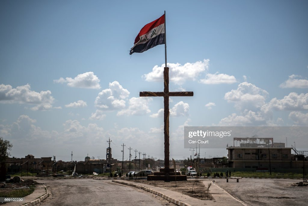 An Iraqi flag flies next to a large crucifix in the nearly deserted predominantly Christian Iraqi town of Qaraqosh on April 16, 2017 near Mosul, Iraq. Qaraqosh was retaken by Iraqi forces in 2016 during the offensive to capture the nearby city of Mosul from Islamic State but it remains almost completely deserted.